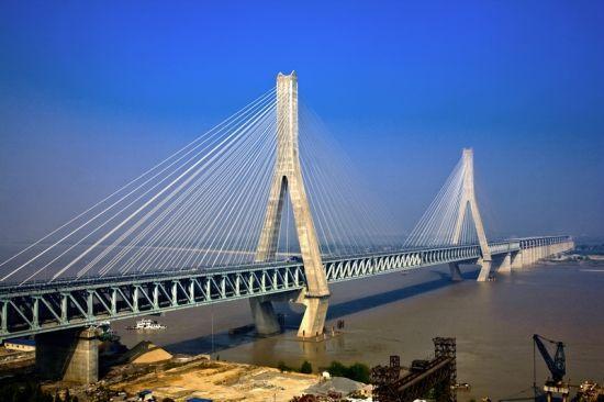 武汉天兴洲大桥图 10日,国家科学技术奖励大会在北京举行,武汉天兴洲大桥三索面三主桁公铁两用斜拉桥建造技术荣获国家科技进步一等奖,该项目是近3年来,唯一被授予国家科技进步一等奖的桥梁工程类项目。 武汉天兴洲长江大桥是中国第一座跨长江的高速铁路桥梁,承载两线高速铁路、两线一级铁路和六车道城市快速路,设计总活载达到351KN/m,桥宽达30m,长江天兴洲江段航运繁忙,要满足船舶通行的要求,主跨必须超过500m。这使得天兴洲大桥成为目前世界上跨度最大、承载最重的公铁两用斜拉桥,特别是高速铁路列车运行对轨道形