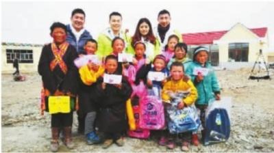 詹冰冰(后排左二)和其他3位伙伴一起将小礼品发给孩子们。