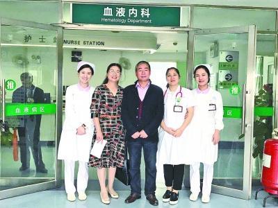 前天,万先生(中)来医院复查后与医护人员合影。(主治医生 周英 供图)