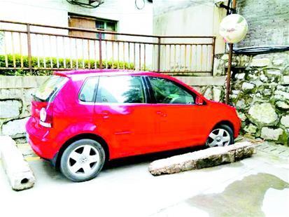 私家车蹭车位被围堵 缴费后物业将障碍物清除