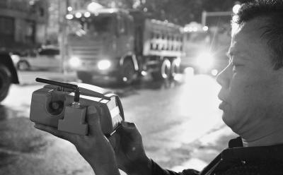 24日晚,督察组在青山工业三路对渣土车经过时的空气质量进行监测。(记者 刘斌 摄)