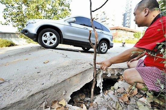 水泥马路受热拱起 过往小轿车底盘频被刮高清图片