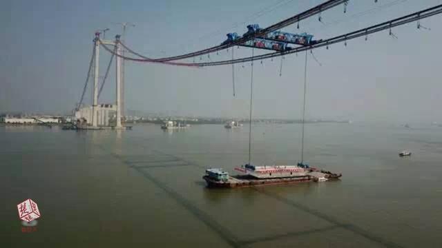 世界最宽悬索首片钢箱梁架设成功 重达272吨