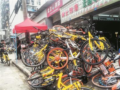 图为:大量共享单车被人堆在路边
