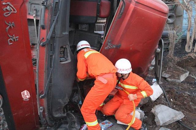 拉煤车侧翻漏油司机被困 两地消防联手救援