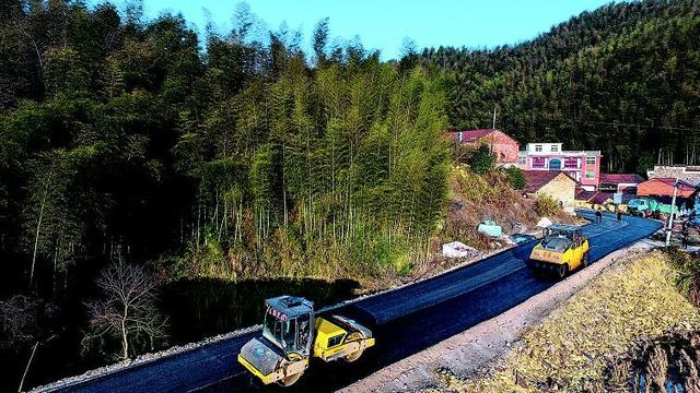 1月11日,大幕乡双垅村至双溪镇李容村的扶贫公路正在进行路面刷黑施工。