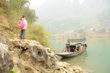 蒙妹玲每天上学都要乘坐简易的小船往返上百米宽的红水河。
