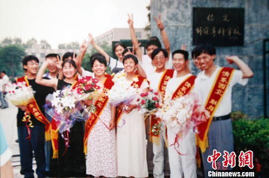 """17年前,15名从河北保定师专(现称保定学院)毕业的学生,带着年轻人的热情来到了新疆南部的""""沙漠边城""""且末县,出发前在校门口合影。 王小军 摄"""