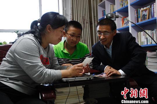 庞胜利、侯朝茹二人给孩子讲第一次到新疆的故事。 王小军 摄