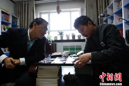 庞胜利给朋友胡浩浩介绍17年前来新疆且末县支教队伍情况。 王小军 摄