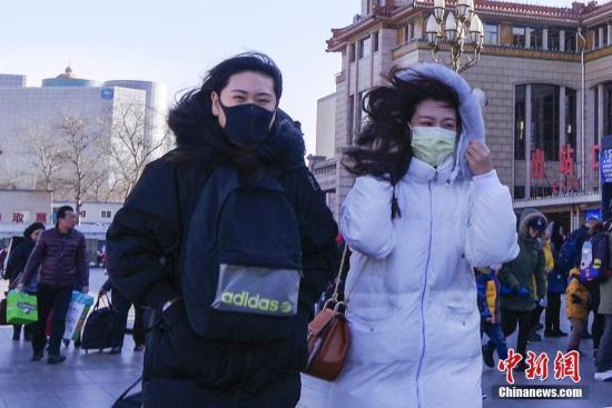 资料图:北京冬季天气持续干冷,民众在寒风中出行。 中新社记者 贾天勇 摄