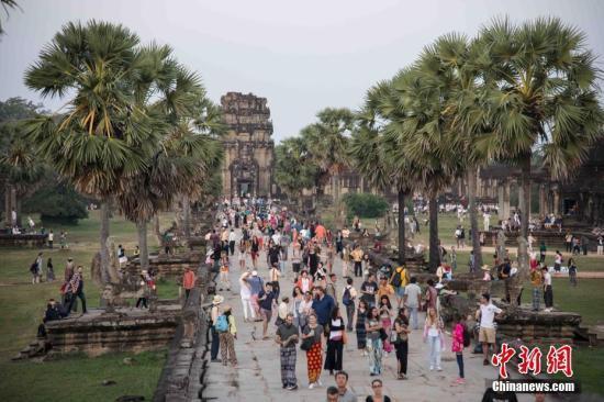 资料图:上千名各国游客守候在柬埔寨暹粒景点——吴哥窟,守候观看日出。 中新社记者 洪坚鹏 摄