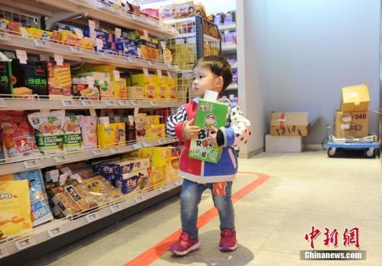 小朋友在超市内挑选商品。刘栋 摄
