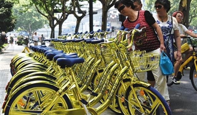 """比之颜色更惹争议的还在于酷骑与P2P平台诚信贷的诸多关联,旧版的酷骑单车两侧印有""""免费骑十次,诚信贷为您买单""""广告。"""