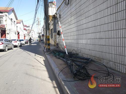 商丘一路段电缆垂地乱如麻 居民呼吁快处理