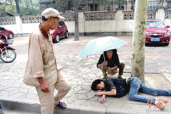 郑州女子路边昏倒 夫妻俩轮流撑伞40多分钟(图)