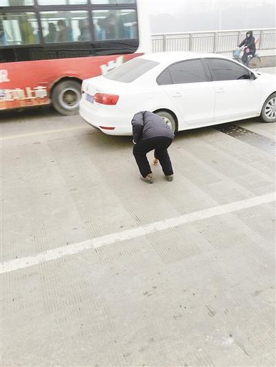漯河一老人滚滚车流中捡硬币 市民:这么做太危险了