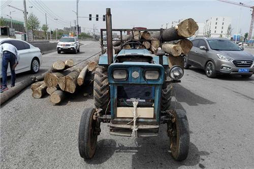 拖拉机掉落圆木剐蹭宝马 被交警打动车主放弃索赔