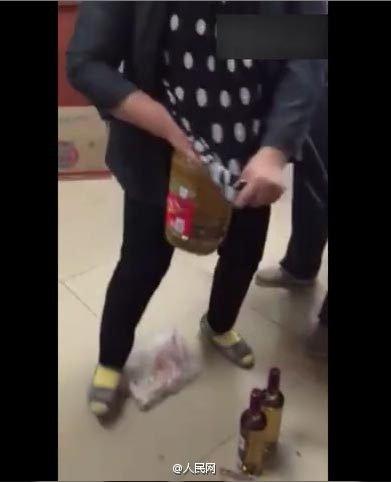 视频中,大妈被要求演示偷窃过程,她先后往裤裆里塞12罐红牛、1