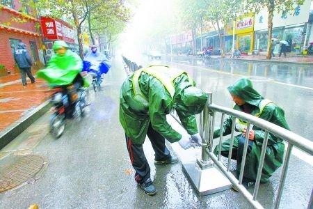 郑州取消路面停车位 警方冒雨安装隔离护栏