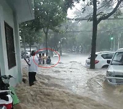 郑州大雨致街头急流冲倒行人 女子弃电车抱树保命