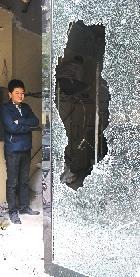 郑州一干洗店男人抡锤砸了邻人干洗店的玻璃门