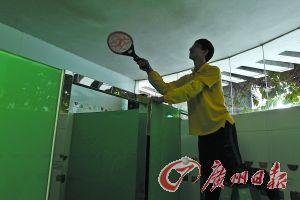 广州近期闹登革热,厕所保洁更严,需要挥动电蚊拍捉拿蚊子。