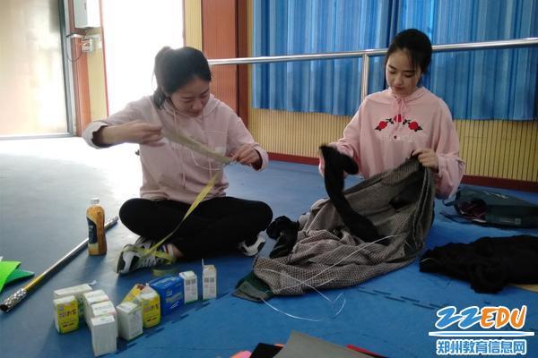 队员康文博(左)和秦梦茹(右)在缝制演出服装