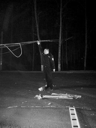 """电缆悬半空成""""拦路虎"""" 周口民警站路中间手举缆线"""