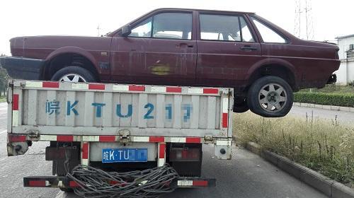 """郑州街头有辆车""""横""""着走 卡车载报废车未固定"""