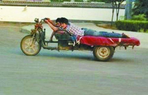 洛阳俩司机趴着开一辆三轮车 各扶一个方向盘