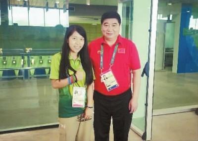 (图为白婷(左)与中国射击队总教练王义夫合影。白婷 供图)