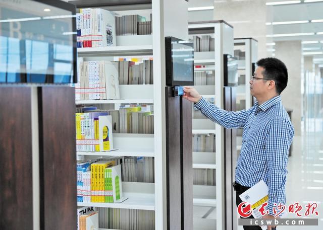 →书架上安装了智能触摸屏,扫一扫手中的图书条码,网络上的精彩书评就会一一呈现。   均为长沙晚报记者  王志伟  摄