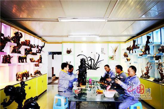 图:学员们在室内摆放的泥塑作品旁进行技术学习、交流。摄影周建华
