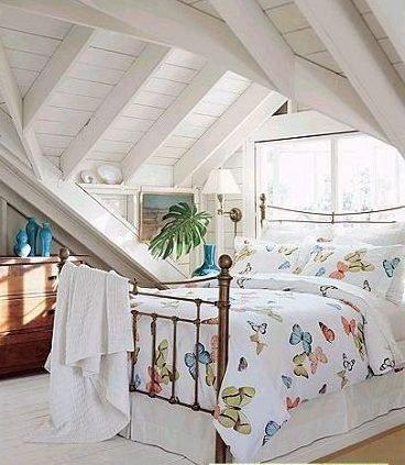 白色的木条墙壁和屋顶,和明媚的床品.高清图片