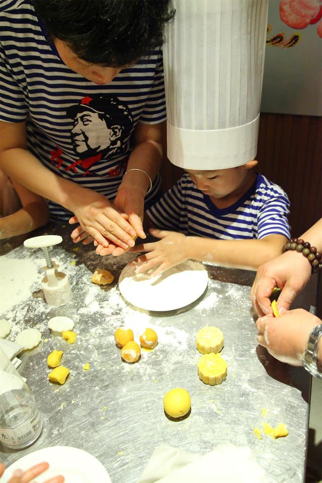 现场小朋友稚嫩的小手在月饼上写上美好祝福,看着小朋友纯真的笔画,家