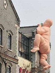 """房上长出""""裸佛攀房""""雕塑"""