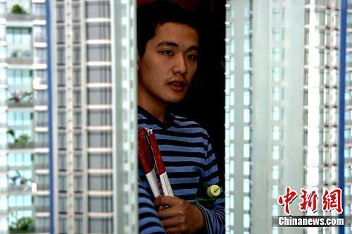 资料图:一位年轻人早早来到福州一售楼部看楼盘。中新社记者 王东明 摄