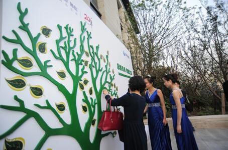 签到处更是别出心裁,嘉宾将名字签在绿色的树叶上,再粘贴至签名墙上的