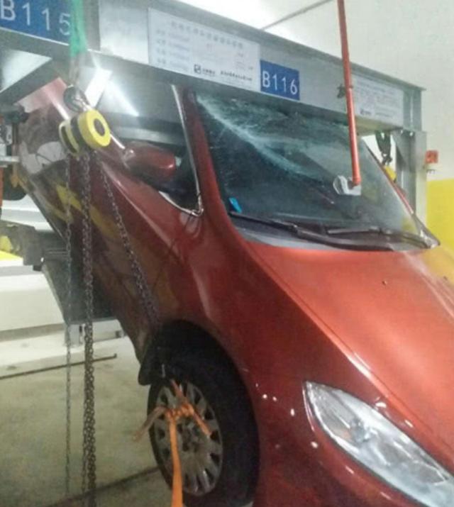 苏州一轿车从立体车库掉下 吊在半空