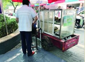 """南京城管给路边摊加""""脚垫""""防止油污弄脏路面"""