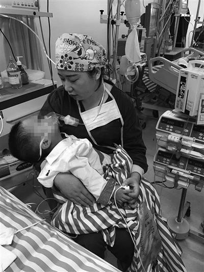 护士刘秀抱着患儿。医院供图