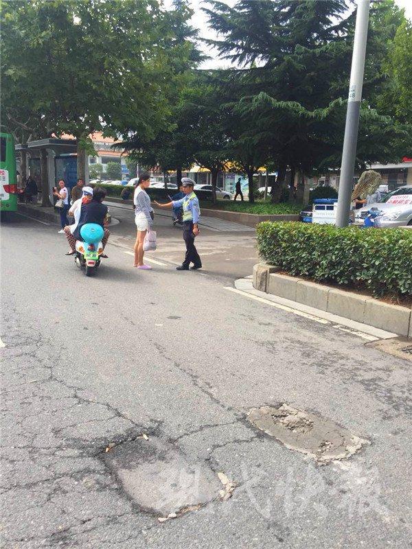 徐州一名短裙女孩翻越马路边隔离护栏 被交警罚款
