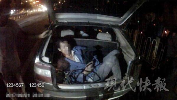 徐州交警发现一辆小轿车挤6人 其中一人坐后备厢