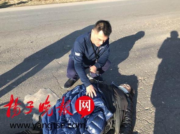 女子骑车摔倒在地 男子脱外套为其取暖