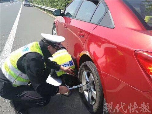 一家三口自驾游高速上遇爆胎 交警当起修车工