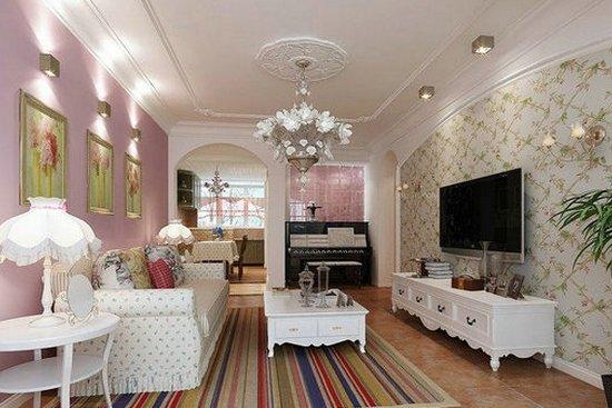欧式田园风格装修图片6 客厅的装修风格为田园式,是一幅小户型客厅的装修图,主要颜色为浅色的,客厅的整体电视墙的壁纸的设计是选用了浅色碎花的系列,圆弧形的边框,白色的实木电视柜子的设计,地板的设计是选用了褐色的仿古砖的设计,整体的白色的软装沙发的设计搭配粉色的墙面,增添了几分甜美的感觉,吊灯的设计是选用了白色的水晶系列,整幅设计图彰显了田园式风格的特点。