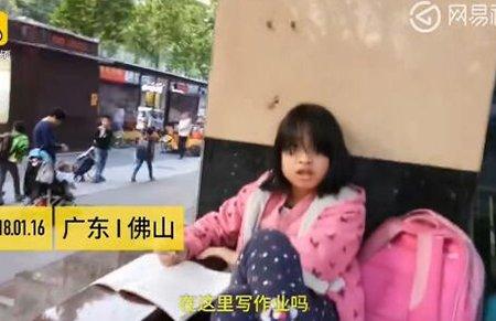 小学生坐路边写作业:怕回家控制不住自己写到很晚