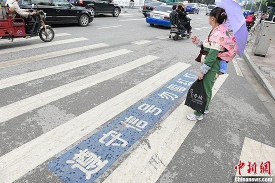图为一名背小孩的妇女在过马路时等候交通信号灯指示.
