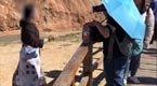 游客翻护栏踩丹霞地貌拍照